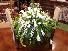 Casket Spray of WHite Calla's Orchids and Roses with Bells of Ireland and mixed Greens.