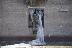 A fighter with the separatist self-proclaimed Donetsk People's Republic army seals a broken window in the town of Debaltseve, Ukraine February 22, 2015. REUTERS/Baz Ratner