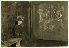 """""""Vance, Trapper Boy, 15 years old. Has trapped for several years in a West Virginia Coal mine at 75¢ a day for 10 hours work. All he does is to open and shut this door: most of the time he sits here idle, waiting for the cars to come. On account of the intense darkness in the mine, the hieroglyphics on the door were not visible until plate was developed. September 1908."""" by Lewis Wickes Hine"""