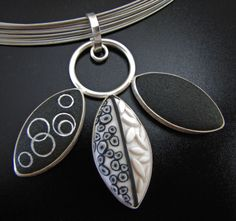 "Pendant | Grace Stokes.  ""Three Petals Pendant, Black and White Series"".  Polymer clay and sterling silver."