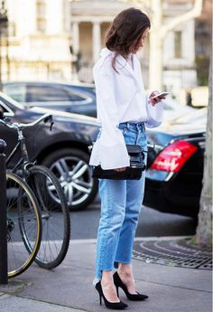 A button-down blouse with bell sleeves is worn with cropped jeans and black pumps