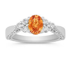 Oval Orange Sapphire and Round Diamond Ring. This bold and colorful ring boasts one oval orange sapphire, at approximately .78 carat TW. Six round diamonds, at approximately .29 carat TW provide the perfect accent. These sparkling gems are crafted in quality 14 karat white gold and the total gem weight is approximately 1.07 carats. #ShaneCoLBD