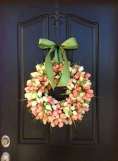 100's of tiny tulips make up this pretty spring door wreath. The bow is unusual since it creates the wreath's hanger, making it practical and decoratively pretty.