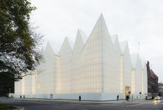 Barcelona-based architecture studio Barozzi Veiga completed a glass-clad Polish concert hall that resembles enormous white quartz embedded in the earth.