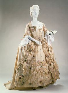 This is a Robe à la Française dress from 1770-80. It is made from a cream colored satin with floral brocade. There is a bow adorning the top of the stomacher. Masses of artificial flowers and lace cover the gown and petticoat. The sleeves end in engageants. The shoes are visible here and are latchet shoes with bows of the same color as the dress on the top.