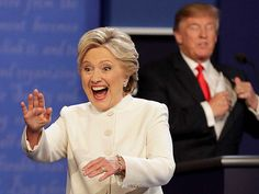 Hillary Clinton waves to the audience as Donald Trump puts his notes away after the third presidential debate