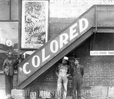 For Coloreds Only | 1938    Image shows several African American youths hanging out around the stairs leading up to the back entrance of a segregated movie theater showing the Tarzan film, Call of the Savage. Anniston, Alabama, 1937. Peter Sekaer, Photographer.