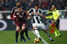 Torino's midfielder Daniele Baselli  (L) fights for the ball with Juventus' forward Mario Mandzukic from Croatia during the Italian Serie A football match between Torino and Juventus at the Grande Torino Stadium in Turin on December 11, 2016. / AFP / MARCO BERTORELLO