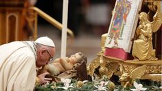 Pope Francis kisses a statue of an infant Jesus during a New Year's Eve vespers mass in St. Peter's Basilica at the Vatican.