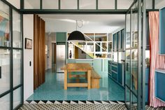 Memphis Colors Meet Greek Details in This Charming Home. The kitchen is flooded with vibrant shades of blue from the cabinets, to the walls to the blue mosaic floor tiles.  A partition of copper pipes, a simple wooden table with bench and hanging black and white basket lamp finish off the look.