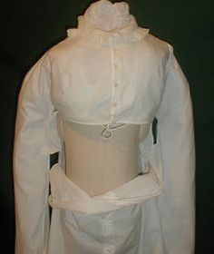 Regency Era Apron Front Dress. 1795-1805 white cotton fall front dress. The front bodice fits to just under the bust line and the fall front skirt ties to the back and would have been pinned in place on the sides. The bodice has a front Dorset button closure. The bodice is lined with a separate linen closure. The collar and sleeve cuffs are trimmed with ruffles. The skirt front is trimmed with decorative Dorset buttons. Several of the buttons are missing. The skirt is unlined.