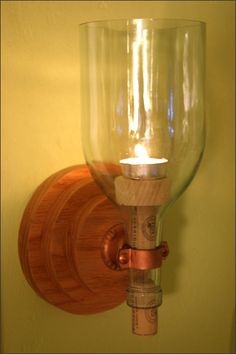 Candle Sconce with Wooden Bracket 4 - This handcrafted candle sconce is a beautiful wine lovers accent whether or not the candle is lit. A set of these candle wall sconces look beautiful on either side of a portrait, either side of a doorway, in the kitchen, or hung by a mantel. Note: Our handcrafted sconces are all unique. Each piece of wood has its own unique appearance so each set of sconces will be unique. The globe is a repurposed 1.5 L wine bottle. After we remove the bottom of the bot…