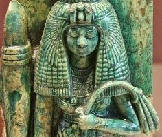 Statuette (steatite and bright green enamel) of Queen Tiye,holding in the left a floral flail;to the left,the right arm of King Amenhotep III.ca. 1391-1353 BCE, now in the Louvre Museum.