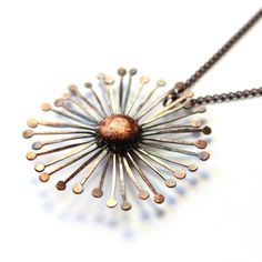 A pure copper dandelion clock pendant inspired by nature themed lino prints. The pendant has been hand made, hammered, oxidised and polished for a unique finish. A polymer clay centre has then been added complete with genuine copper leaf which has been antiqued and finished with laquer. The pendant is hung on an antique copper plated chain with a trigger clasp fastening. Available in a 16 or 18 inch length chainThe dandelion is approximately 4 cms in diameterAs the penda...