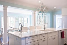 Contemporary kitchen features white shaker cabinets in island topped with white marble and two sinks illuminated by turquoise beaded chandelier.