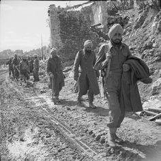 Battle Cassino January-May 1944 (NA 12895)   Second Phase 15 February - 10 May 1944: Indian troops pass bomb shattered buildings on the outskirts of Cassino town.