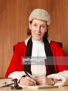 Stock Photo : Female judge sitting at desk, smiling, portrait, close-up