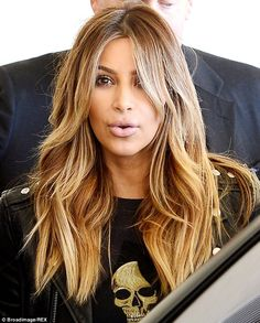 Kim wore her blonde hair in beachy waves in December 2013, out about in LA with her sister...