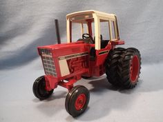 This Die Cast Ertl International 1586 Tractor w/Cab #463 - 1:16 Scale - NIB - is new old stock in original box. The box and tractor are crisp & clean and in like new condition. It has only been out of box to photograph and insert Smoke Stack. FEATURES: Wide Front .......... 1:16th scale Replica of International 1586 Tractor w/ Protective cab