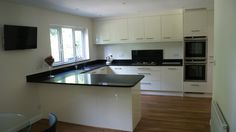 Modern gloss white kitchen in Ascot Berkshire with Karndean flooring and black granite work tops designed & fitted by Orchardkitchens.com of Egham Surrey