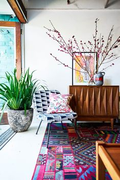 This living room retreat, featuring a bold geometric print chair and a multi-coloured rug opens out onto the courtyard, effectively doubling its size. The vintage mid-century modern sideboard was picked up from a kerbside and upcycled. Photography: John Paul Urizar | Styling: Louise Bickle