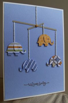 By Tilly. Cute baby card using an elephant punch, string, paper strips, and a brad.