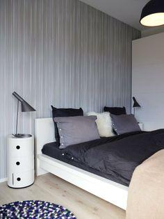 GJENNOMFØRT SOVEROM: Soverom gårogså i hvitt og grått, med anslag av lilla i teppetfor å skape spenning. AJ-leselamper og nattbordComponibili fra Kartell. Sengetøyet er fra Himla.