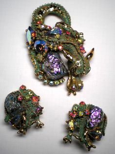 HAR brooch and clip earrings are a dragon with lava rock, aurora borealis stones and green enamel. Red aurora borealis stones for the eyes.