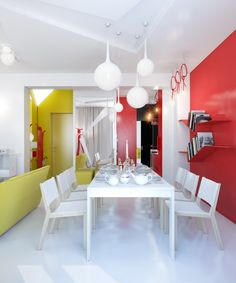A great open-plan living space . . . the use of yellow and red against a white background and white contemporary dining furniture gives it a really cool, modern look and coordinates with the hallway uniting the different areas.