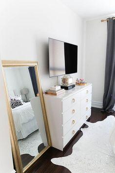 Chic bedroom features a flatscreen TV atop a white Ikea Malm Dresser adorned with gold ring hardware next to a gold leaf leaning mirror alongside a metallic cowhide rug.