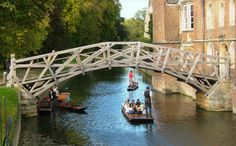 The Mathematical bridge with langorous punts gliding along the river Cam. Summer in Cambridge