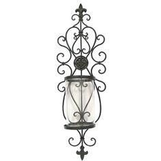 """Add a touch of vintage elegance to your decor with this Iron Swirl Wall Piece with Glass. Gorgeous with a candle, you can also vary the look by the season with greenery or other decorator items.    It measures approximately 7 1/2"""" wide x 24 1/2"""" tall."""