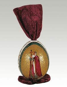 1896 ca. Easter Egg with Sainted Prince Vladimir.                                                                   Porcelain, overglaze polychrome painting, gilding. Oval medallion on golden background with plant depicts Sainted Prince Vladimir wearing crown, red mantle, holding cross. Reverse, green frame with garland of leaves, pale blue background.                                                        State Hermitage Museum, Russia.                suzilove.com