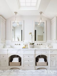 Completely redone with a fresh, simple feel and attention to detail, the master bathroom features custom built-in double vanities topped with honed Calacatta, installed by JB Tile & Stone. Pendants above are by Waterworks. Wall-mounted faucets are from Lefroy Brooks' 1930s Mackintosh range.