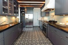 gray beaboard cabinets; black counters; Moroccan-style tile flooring; rustic beams