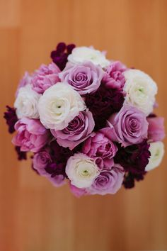 Breanna's bouquet featured purple roses and peonies and white ranunculuses.  Venue: Tre Bella