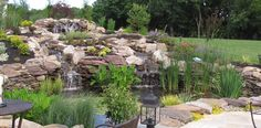 Patio view of a beautiful pond with crashing waterfalls and double split stream.