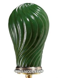 A Jewelled Gold-Mounted Nephrite Cane Handle By Fabergé, apparently unmarked, scratched inventory number 50856. Of baluster form, the spiral-fluted hardstone body above rose-cut diamond and gold borders, apparently unmarked, scratched with inventory number under base