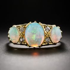 A classic three-stone ring from Birmingham, England - circa 1902, highlighting a colorful trio of multi-chromatic opals enhanced with two pair of small old mine-cut diamonds glistening from within triangular settings. This traditional Victorian jewel is crafted in rich 18 karat yellow gold and is fully hallmarked inside the ring shank