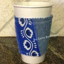 """This adorable and functional coffee """"cozy"""" is one of a kind!  Recycling the cardboard sleeve from a local coffee shop, it is sandwiched in between a piece of denim and a blue bandana print fabric that was left over from another project.  No scraps go to waste at Re-Love Boutique!   Wraps around..."""