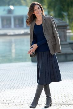 Navy and gray sweater skirt with herringbone pattern. Long sleeve tee. Boots. Jacket that reflects neutral shade of boots.