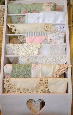 Wooden shabby chic rack with vintage doilies and linens