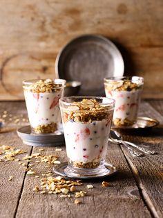 Cremiger Joghurt mit Honig, Beerenfrüchten und Müsli eingeschichtet.