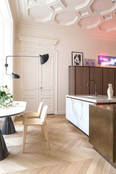 The pink neon sign casts a soft rosy glow in this Paris apartment. The architecture is ornate, but the midcentury furnishings keep the space from looking overly feminine.