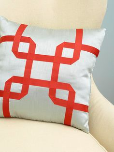 Modern Geometry  Turning a plain pillow into a piece of art is as simple as adding a ribbon. Iron fusible web to the back of the ribbon, then remove paper backing. Pin prepared ribbon in desired design onto pillow cover; iron on. Reinsert pillow form.