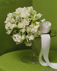 An ethereal bouquet gets its elegance from fluttery sweet peas and emerald-striped lady's slipper orchids, bundled together with white satin ribbon.