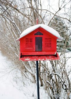 Red Birdhouse in White Snow
