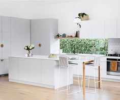 This budget-friendly, Scandinavian style kitchen features timber detailing and V-groove panelling in soft grey to bring texture and visual warmth to the space, while a white tiles and benchtop keep it light and bright.