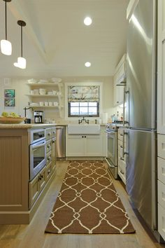 What a beautiful kitchen... I'm not sure about this rug... Not about the color/style but the fabric, for a kitchen usage.