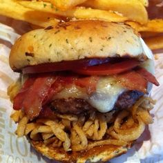 Spread a generous amount of peppercorn spread on both slice of the bun. Stack onion straws, burger patty, tomato, and bacon. Enjoy!!